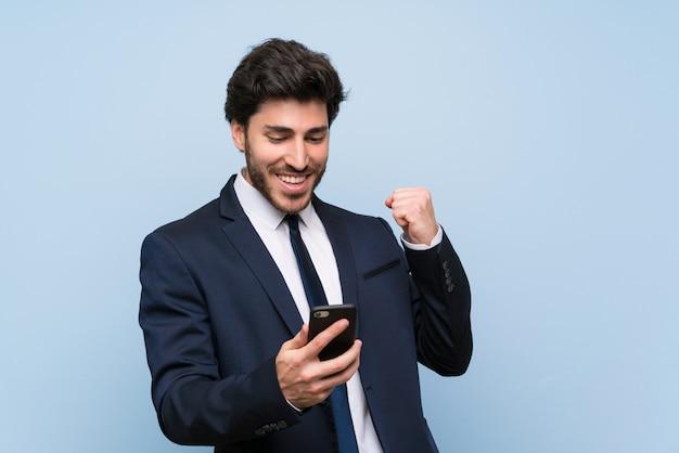 Biznesmen nad odosobnioną błękit ścianą z telefonem w zwycięstwo pozyci