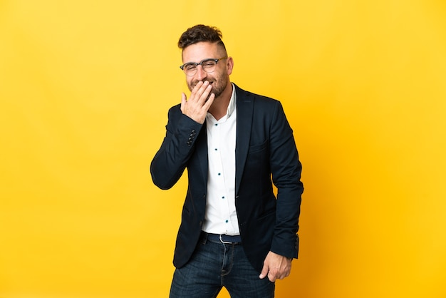 Biznesmen nad odosobnioną żółtą ścianą szczęśliwy i uśmiechnięty obejmujące usta ręką