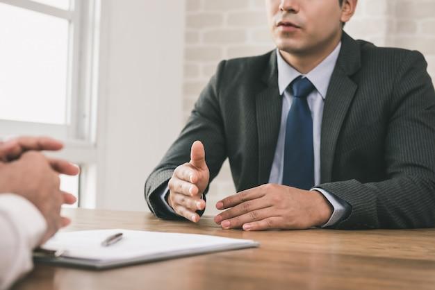 Biznesmen negocjuje z klientem przy stołem