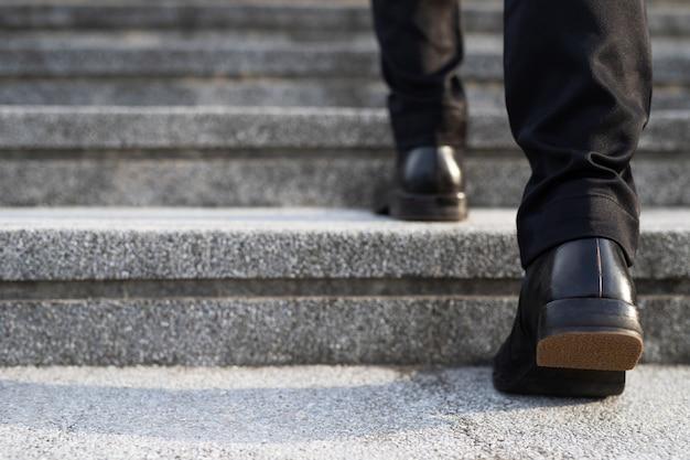 Biznesmen noga chodzenie po schodach w mieście. klatka schodowa.