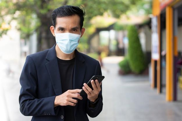 Biznesmen nosi maskę chroniącą przed koronawirusem covid19