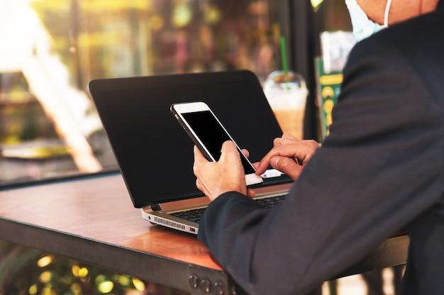 Biznesmen nosić maskę medyczną za pomocą telefonu w kawiarni