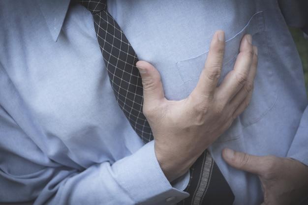 Biznesmen o ból w klatce piersiowej i atak serca, ręka trzyma bolesne.