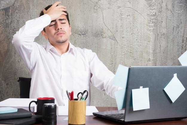 Biznesmen o bólu głowy przy biurku.