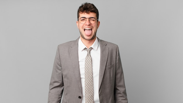 Biznesmen o pogodnym, beztroskim, buntowniczym nastawieniu, żartuje i wystawia język, bawi się
