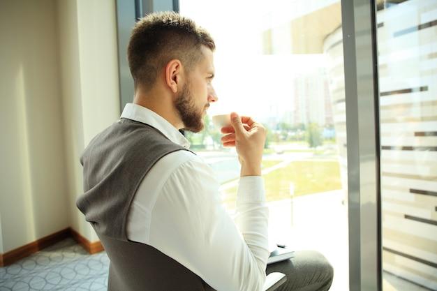 Biznesmen o przerwie na kawę i relaks w oknie.