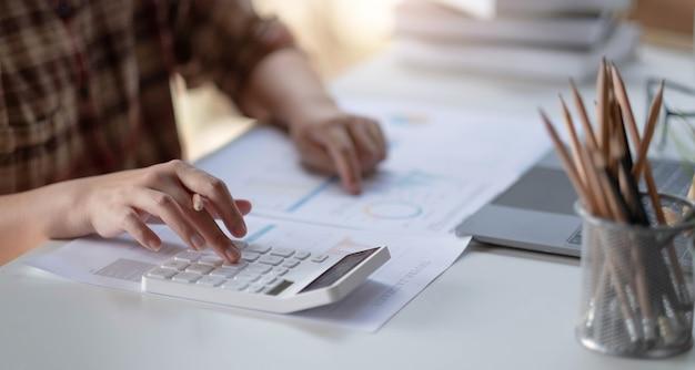 Biznesmen oblicza finanse z papieru milimetrowego na stole na koszt domowego biura wieczorem.