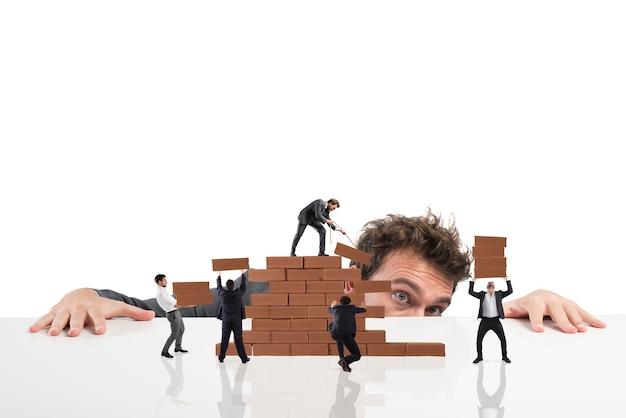 Biznesmen obserwuje pracę zespołową przedsiębiorców pracujących razem, budując mur z cegły