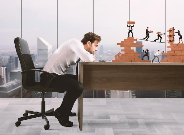 Biznesmen obserwuje pracę zespołową przedsiębiorców pracujących razem przy konstrukcji z cegieł