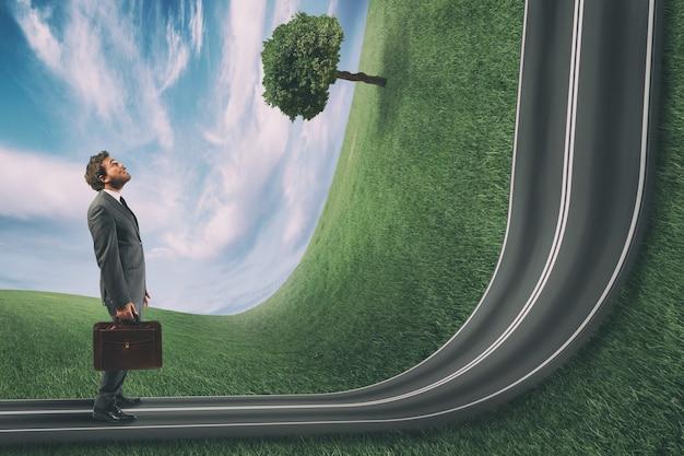 Biznesmen obserwuje przed sobą drogę pod górę