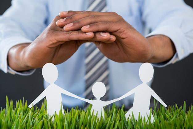 Biznesmen ochrony papieru wyciąć ręką rodzinę, dom i samochód