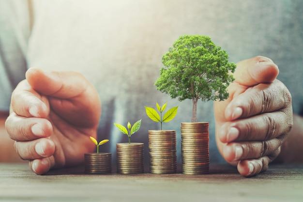 Biznesmen ochrony pieniądze na stole z drzewem