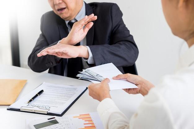 Biznesmen odmawia lub odrzuca pieniądze w kopercie
