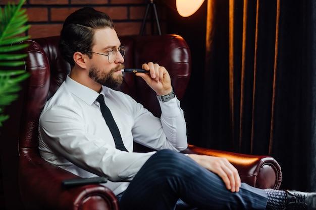 Biznesmen odpoczywa i relaksuje się siedząc na kanapie w luksusowym pokoju