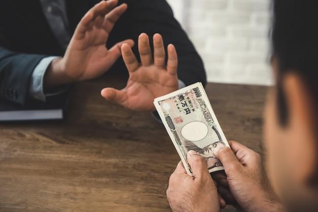 Biznesmen odrzuca pieniądze, banknoty japońskiego jena, podane przez jego partnera