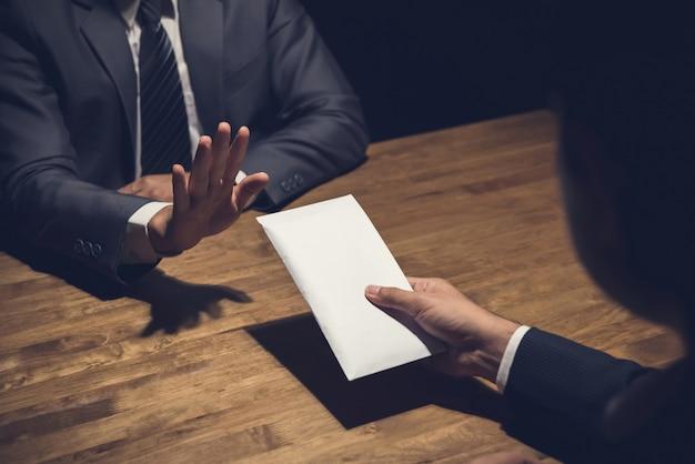 Biznesmen odrzuca pieniądze w białej kopercie oferowanej przez jego partnera w ciemności
