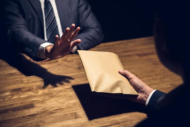Biznesmen odrzuca pieniądze w kopercie