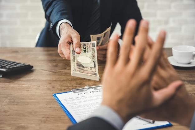 Biznesmen odrzucający pieniądze, japońską walutę yen, od swojego partnera