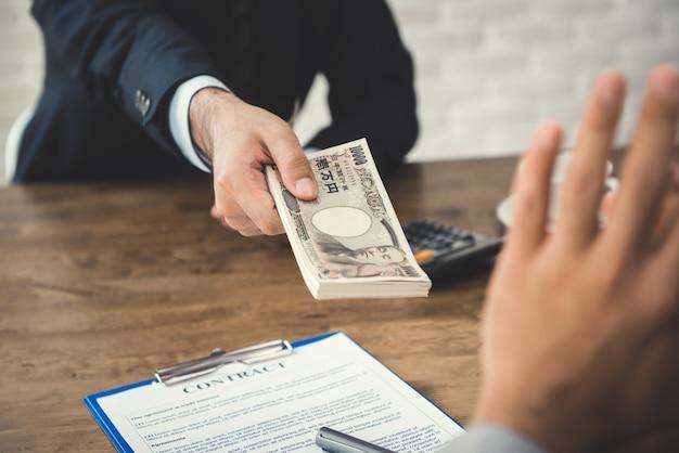 Biznesmen odrzucający pieniądze, japońskie banknoty jenowe, oferowane przez jego partnera podczas zawierania umowy