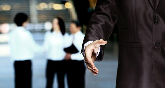 Biznesmen oferuje uścisk dłoni na tle budynków biurowych
