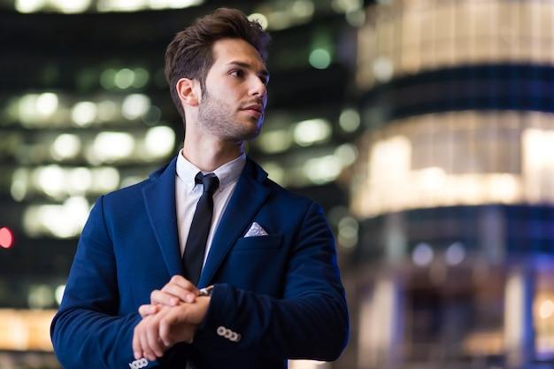 Biznesmen ogląda czas w vening w nowożytnym mieście