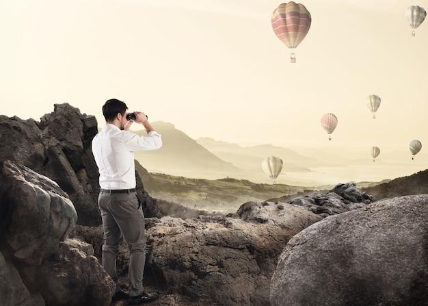 Biznesmen, opierając się na skale, oglądając przez lornetkę balony na ogrzane powietrze na niebie