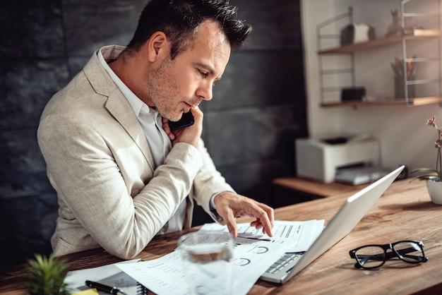 Biznesmen opowiada na mądrze telefonie i robi papierkowej robocie w jego biurze