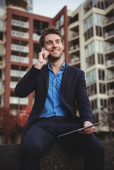 Biznesmen opowiada na telefonie komórkowym i trzyma cyfrową pastylkę