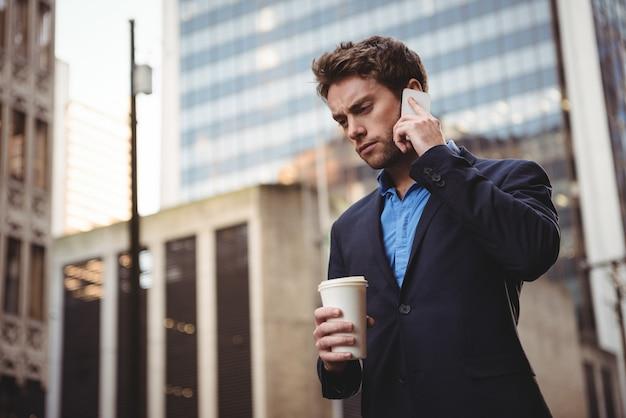 Biznesmen opowiada na telefonie komórkowym i trzyma kawę