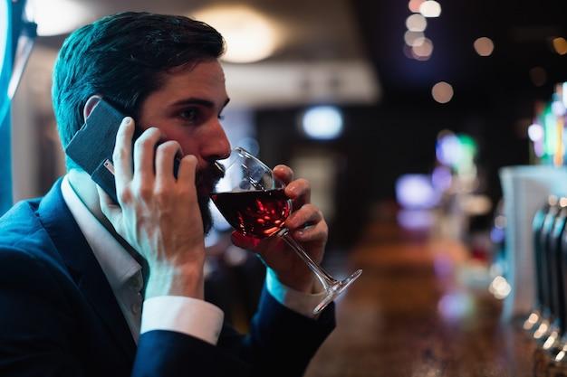 Biznesmen opowiada na telefonie komórkowym podczas gdy mieć szkło wino