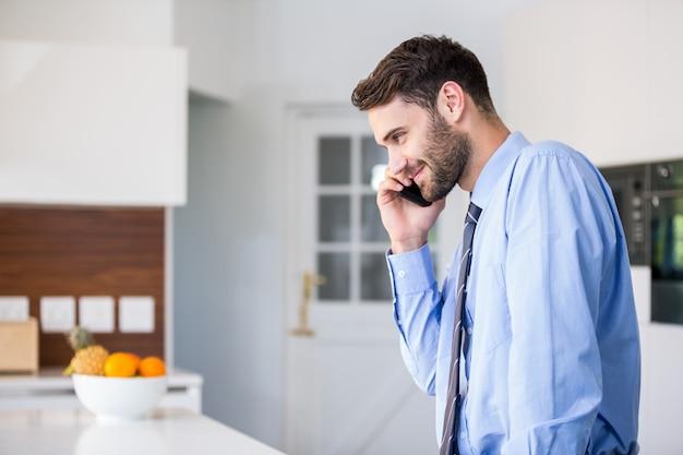 Biznesmen opowiada na telefonie komórkowym w kuchni