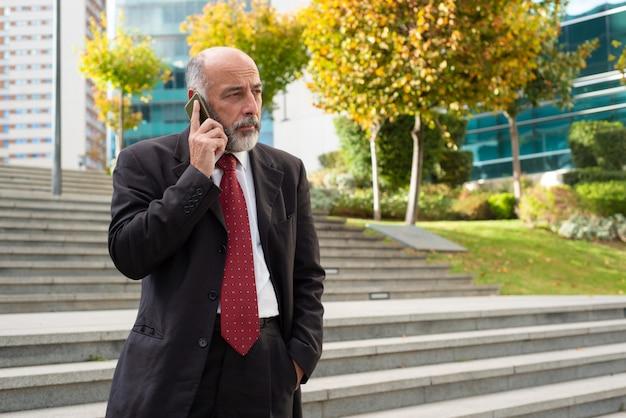 Biznesmen opowiada smartphone i patrzeje daleko od