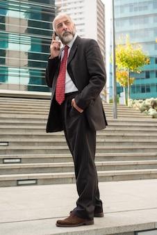 Biznesmen opowiada telefonem komórkowym i patrzeje daleko od