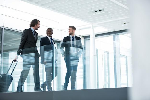 Biznesmen opowiada z kolegami podczas gdy chodzący
