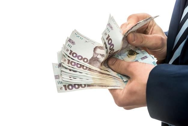 Biznesmen osiągał ogromne zyski, pokazując dużo pieniędzy. mężczyzna w garniturze trzyma pakiet nowych banktonów ukrainy. 1000 hrywien
