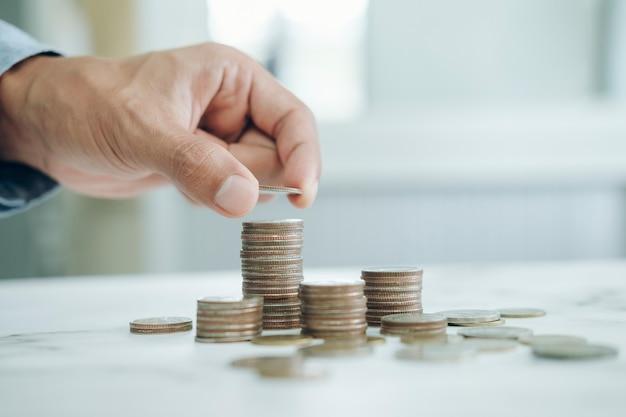 Biznesmen oszczędzania pieniędzy koncepcja. dłoń trzymająca monety wkładająca szklankę do dzbanka