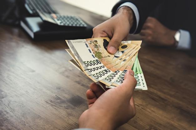Biznesmen otrzymujących pieniądze, rachunki w walucie wygranych w korei południowej, ręka w rękę