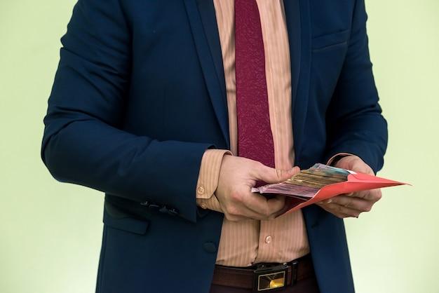 Biznesmen otrzymuje pieniądze jako łapówkę w kopercie. mężczyzna daje w kopercie całe mnóstwo hrywien ukraińskich