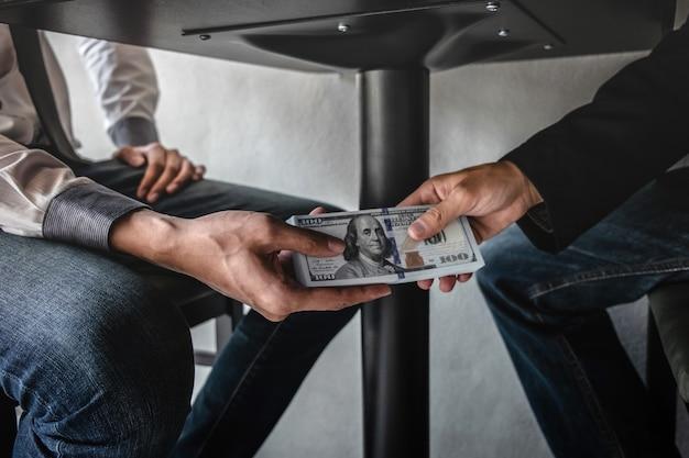 Biznesmen otrzymuje pieniądze łapówki pod stołem dla ludzi biznesu, aby dać sukces umowy sprzedaży