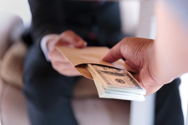 Biznesmen otrzymywa pieniądze pod stołem - anty przekupstwa i korupci pojęcia