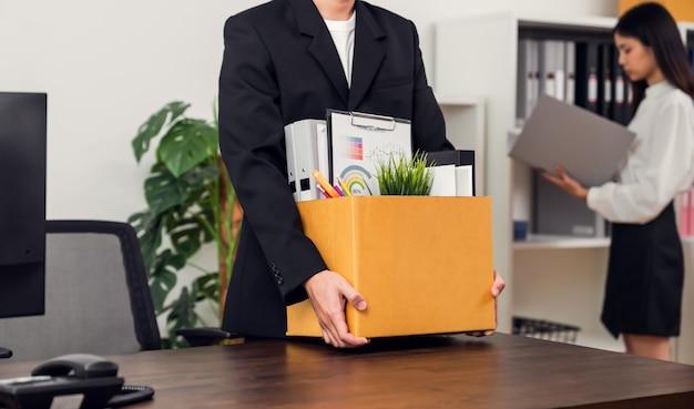 Biznesmen pakuje i trzyma brązowe pudełko kartonowe z dokumentami.