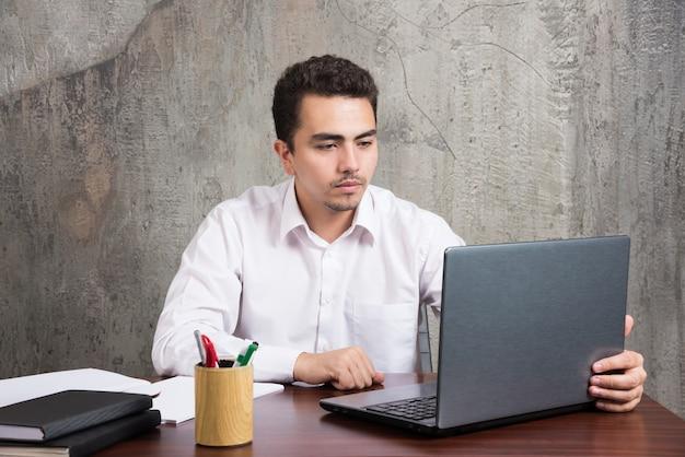Biznesmen, patrząc na laptopa i siedząc przy biurku. wysokiej jakości zdjęcie