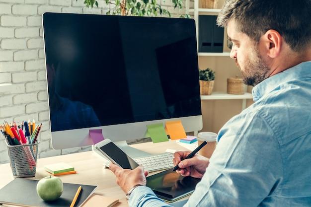 Biznesmen patrząc na monitor komputera podczas dnia pracy w biurze
