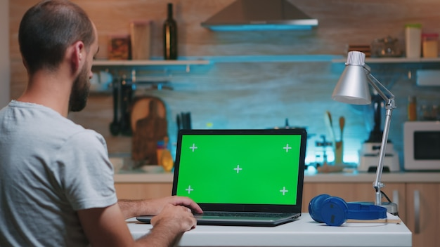 Biznesmen patrząc na zielony ekran monitora siedzi w domu w kuchni. freelancer ogląda monitor pulpitu z zieloną makietą, kluczem chrominancji, w nocy pracując w godzinach nadliczbowych.