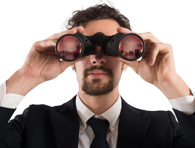 Biznesmen patrząc przez lornetkę miasto. patrząc na przyszłą koncepcję
