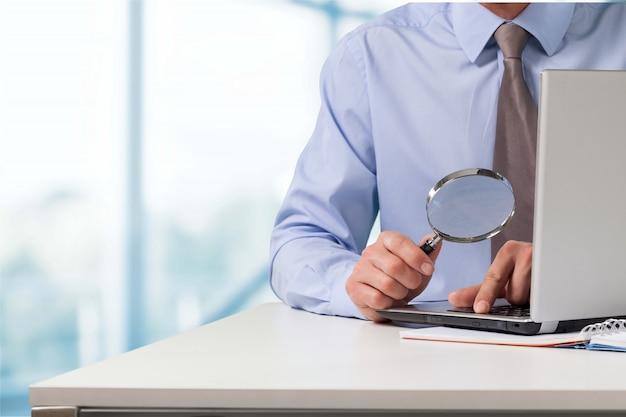 Biznesmen patrzący na swojego laptopa przez szkło powiększające