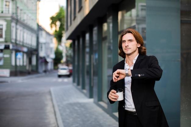 Biznesmen patrzeje jego zegarek z kawą