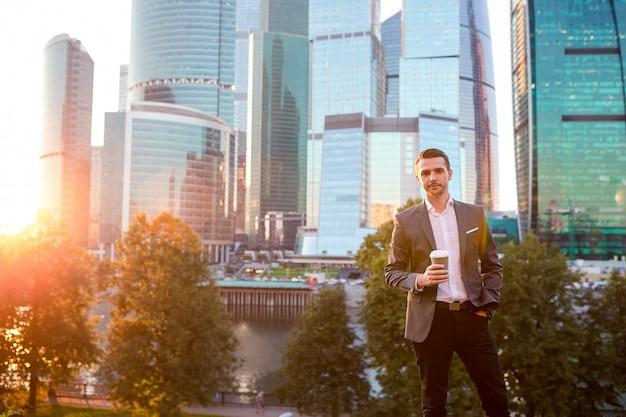 Biznesmen patrzeje na kopii przestrzeni podczas gdy stojący przeciw szklanemu drapaczowi chmur