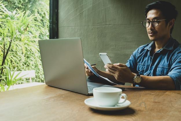 Biznesmen patrzeje telefon komórkowego i trzyma papierkową robotę z laptopem na stole