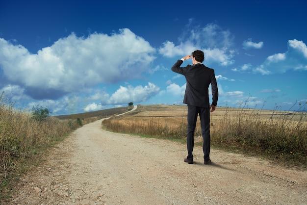 Biznesmen patrzy na horyzont z wiejskiej drogi